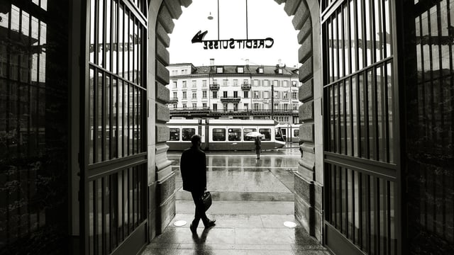 Mann steht in Eingang der Credit Suisse