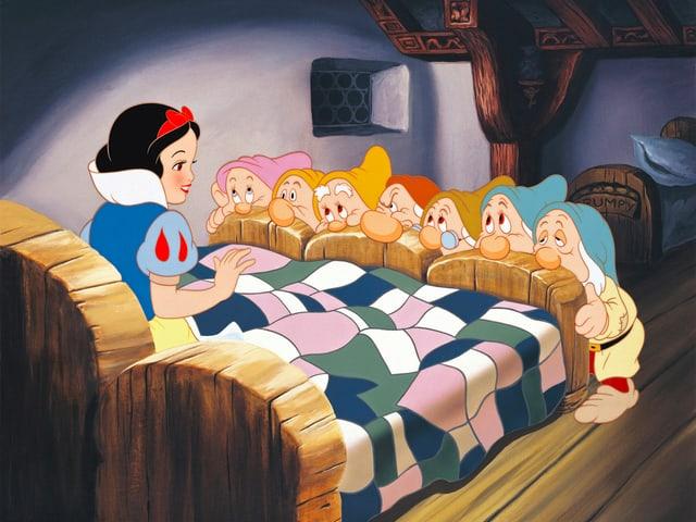 Schneewitchen, im Bett sitzend, vor ihr die 7 Zwerge.