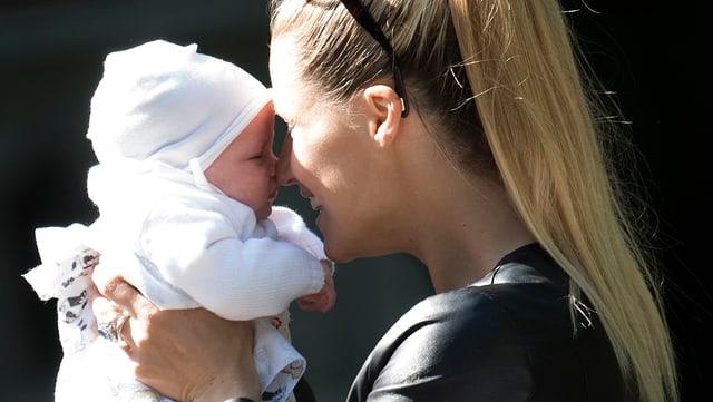Michelle Hunziker hält lachend ihr Baby vor ihr Gesicht.