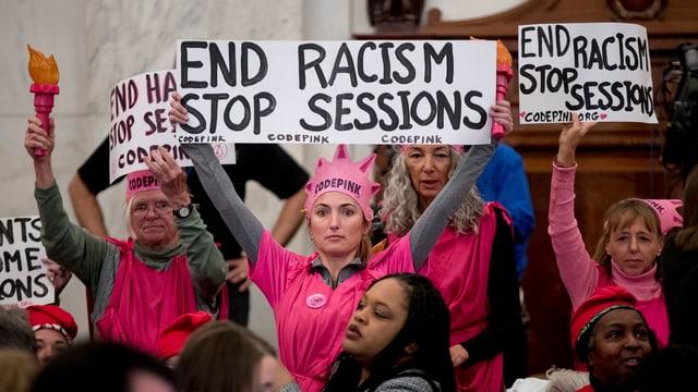 Mehrere Frauen in pinkfarbener Kleidung halten Plakate in die Höhe.