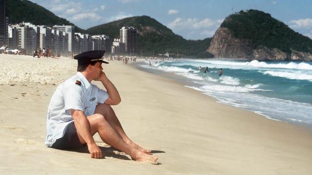 Mann in Piloten-Uniform sitzt am Strand.