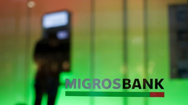 L'inscripziun MigrosBank, davos ina persuna vid in bancomat.