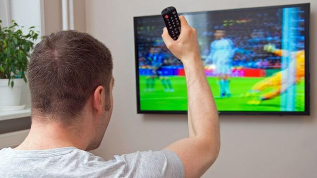 Ein Mann schaut ein Fussballspiel und jubelt mit der Fernbedienung in der Hand.