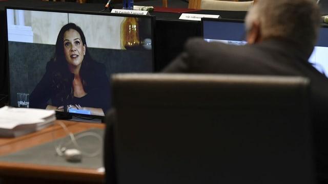 Frau auf Bildschirm in Regierungsgebäude