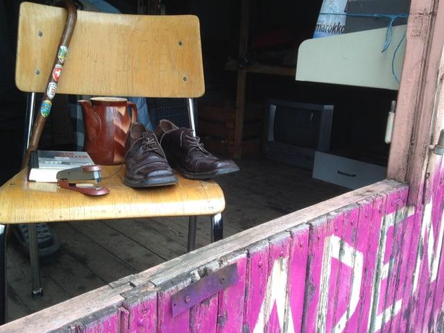 Stuhl mit diversen Gegenständen, u.a. ein paar Schuhe, ein Buch, ein Krug.