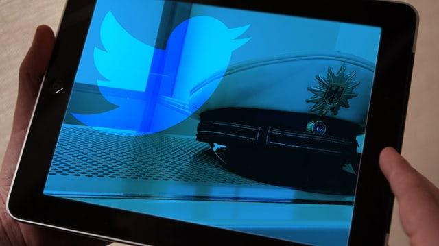 Auf einem Bildschirm ist der Twitter-Vogel und ein Polizeihut zu sehen.