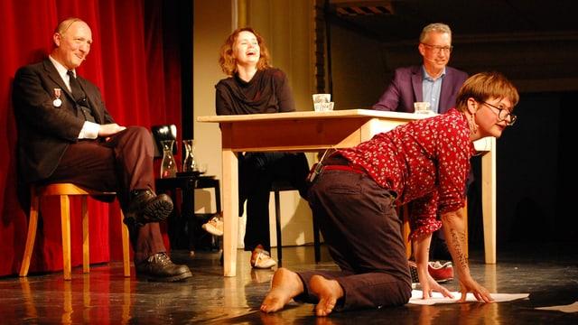Drei Menschen am Tisch schauen einer Artistin zu.