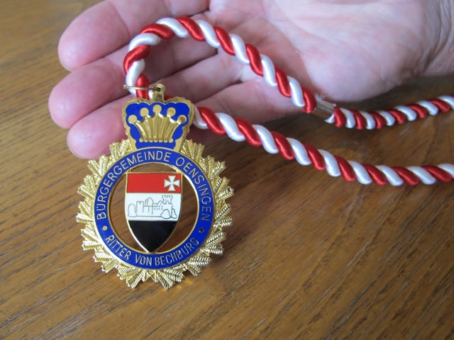 Medaille an einem rot-weissen Bändel.