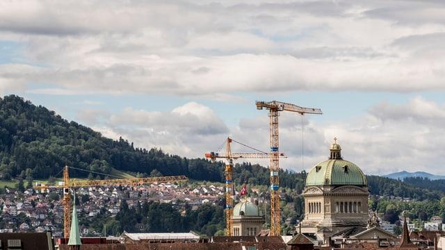 Bundeshaus mit drei Baukränen in der näheren Umgebung.