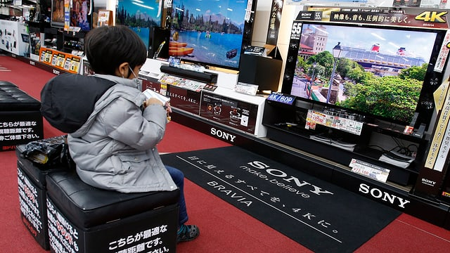 Ein kleiner Junge spielt auf seinem Smartphone vor einem grossen TV-Bildschirm.