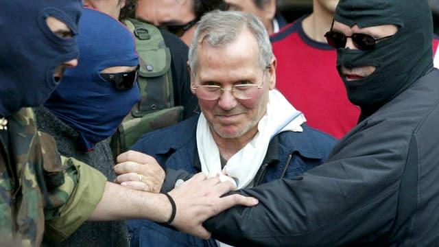 Der Mafiaboss mit Brille und ergrautem Haar wird von Polizisten mit Gesichtsmasken und Sonnenbrillen vorgeführt.