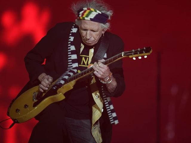 Keith Richards spielt Gitarre vor rotem Hintergrund