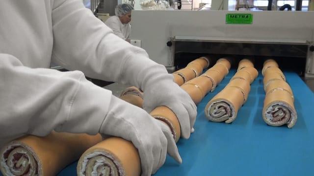 Industrielle Produktion von Rouladen, zwei Hände mit weissen Handschuhen