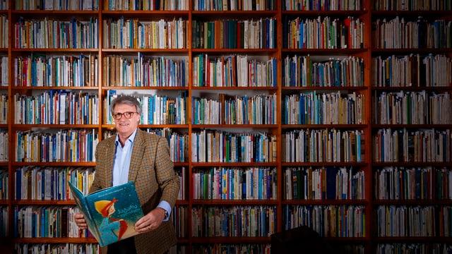 Ein Mann steht mit einem Buch vor einem riesen Bücherregal.