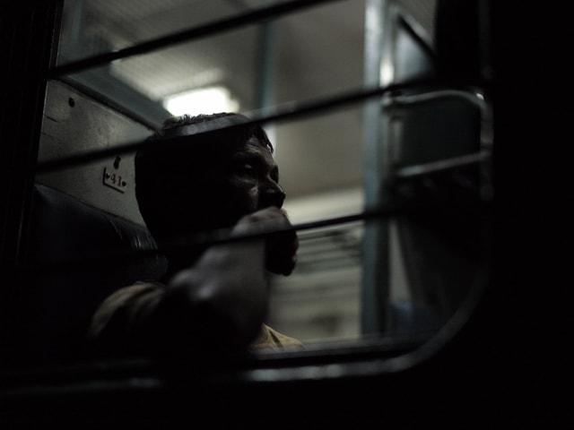 Ein Mann im Zug, alles dunkel, schwer zu beschreiben, sorry.