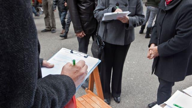 Unbekannte Menschen füllen auf einer Strasse Unterschriftenbögen für eine Volksinitiative aus.