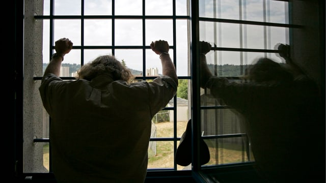 Mann im Schattenriss vor vergittertem Fenster