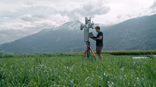 Mann steht mit einem Stativ auf einer Wiese vor Bergkulisse