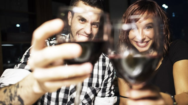 Junges Paar prostet sichtlich angeheitert der Kamera zu.