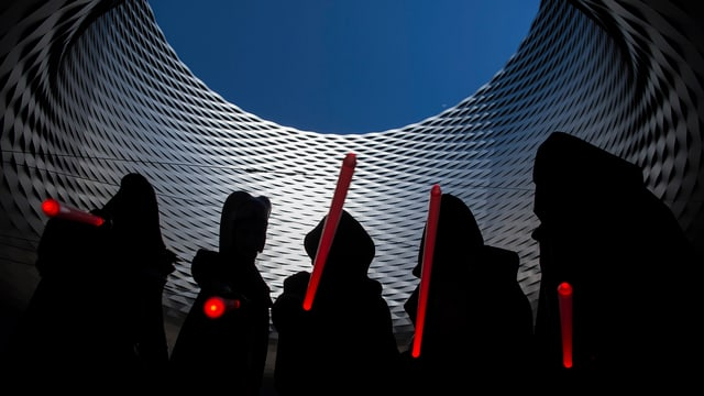 Vier Gestalten halten rote Lichtschwerter in die Höhe, im Hintergrund die Messe Basel.