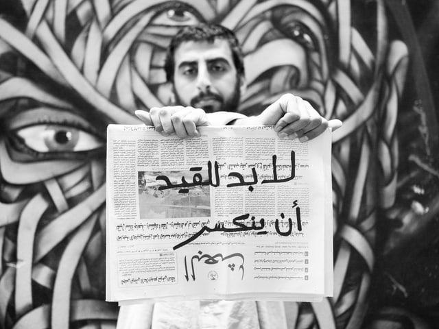 Ein Mann mit Bart hält eine arabischsprachige Zeitung vor sich.