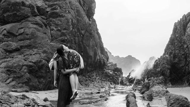 Eine junge Frau trägt eine andere junge Frau, mit hängenden Armen und Beinen, auf der Schulter. Im Hintergrund eine rauhe Fluss- und Berglandschaft.
