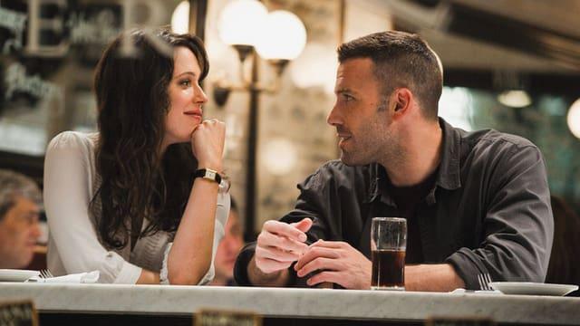 Eine Frau und ein Mann sitzen an einer Bar und sprechen miteinander.
