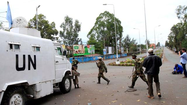 Rebellen der M23 laufen um ein gepanzertes UNO-Fahrzeug.