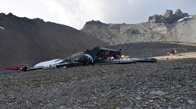 Flugzeugwrack vor Bergkulisse, im Hintergrund ist ein Helikopter sichtbar.