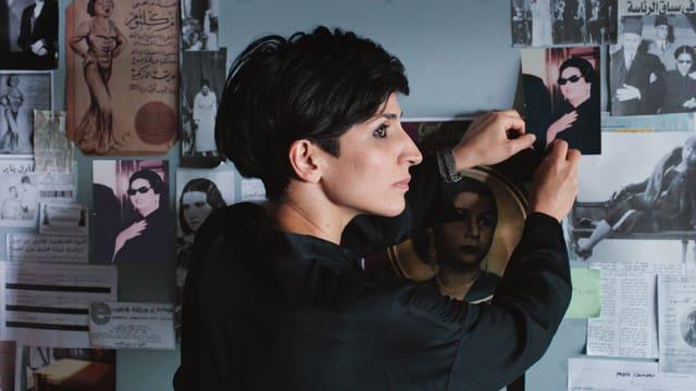 Eine Frau hängt Bilder von einer Wand ab.