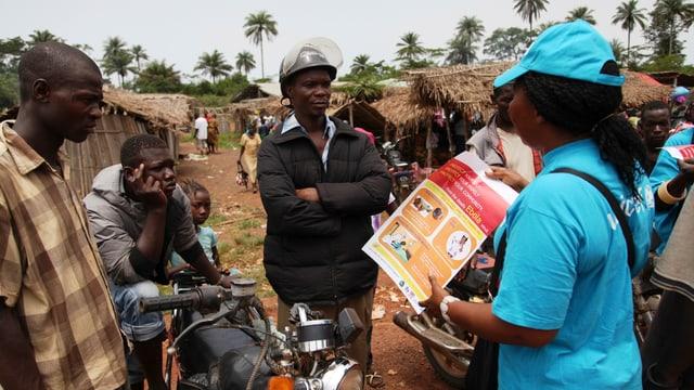 Eine Fachperson klärt Afrikaner über Ebola auf.