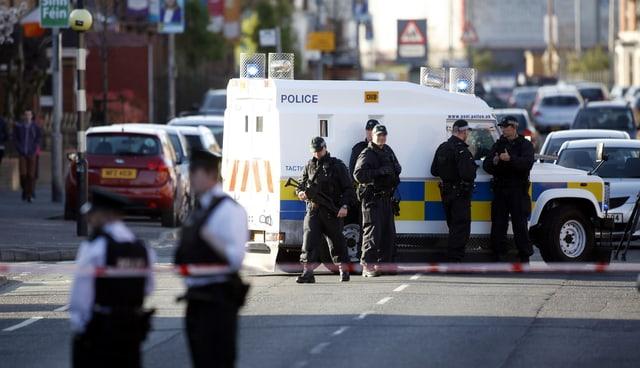 Polizei an einem Polizeifahrzeug.