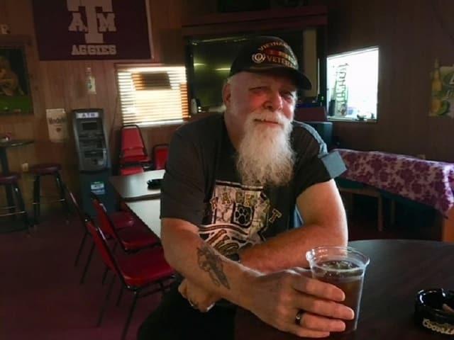 Mann mit Bart trinkt Bier.