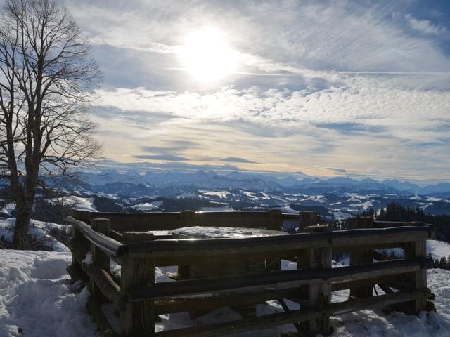 Vom sanften Emmentaler Hügel aus sieht man in die Berner Alpen. Am Himmel ziehen Wolkenfelder auf, und die Sonne scheint nur schwach durch die Schleierwolken durch.