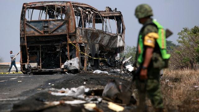 Der ausgebrannte, verkohlte Reisecar, davor ein Soldat in grüner Leuchtweste