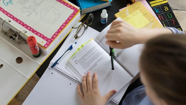 In maun d'uffant e bler material da scola per la preparaziun da l'examan d'admissiun.