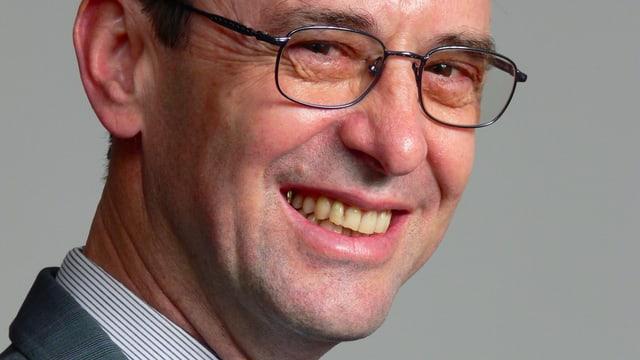 Hans Jakob Roth lacht in die Kamera mit Brille auf der Nse und leicht unrasiert