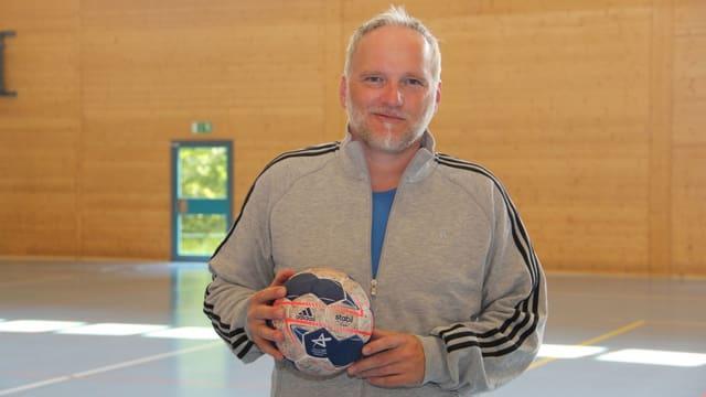 Ein Mann posiert mit einem Handball