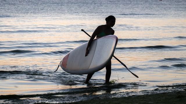Frau mit SUP-Ausrüstung verlässt das Wasser.