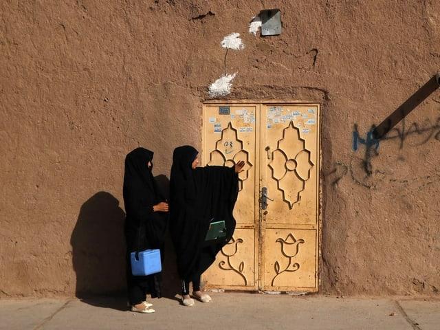 Zwei Frauen tragen eine blaue Kühlbox (vermutlich mit einer Polioimpfung darin) zu einer Haustüre. Beide Frauen tragen eine Burka.