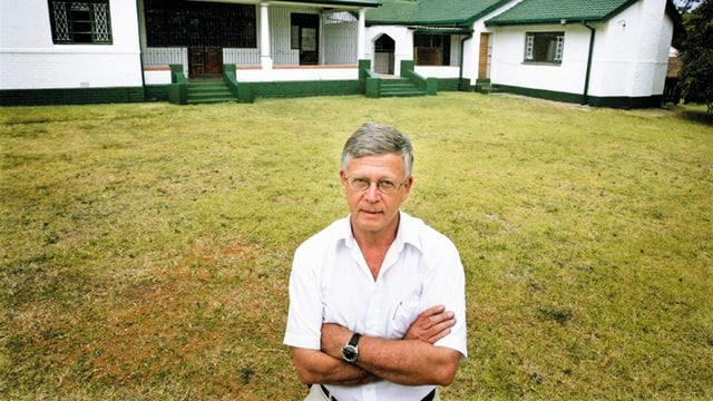 Mann mit Brille vor einem Haus.
