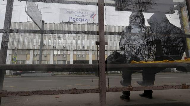 Menschen sitzen an Bushaltestelle vor Gebäude