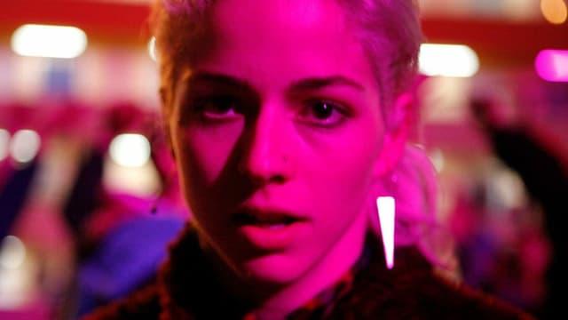 Filmszene: Nahaufnahme des Gesichts einer Frau, der Hintergrund ist verschwommen.
