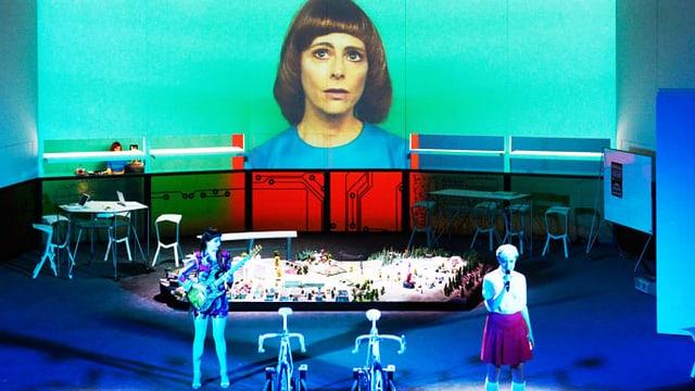 Zwei Fahrräder stehen am Bühnenrand daneben eine junge Frau. Im Hintergrund ist das Bild einer andern Frau gross an die Wand projiziert.