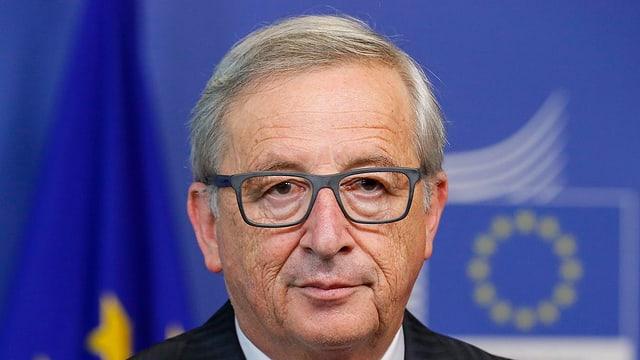 Jean-Claude Junkcer bei einer Pressekonferenz. Im Hintergrund die EU-Symbole.