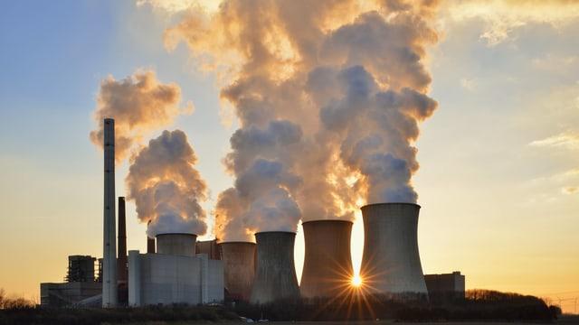 Kühltürme und Schlote eines Kraftwerks rauchen stark.