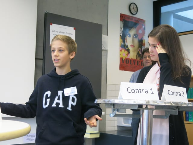 Ein Knabe und eine Mädchen stehen an einem Tischchen.
