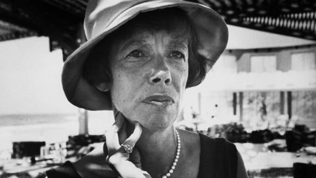 Schriftstellerin Jane Bowles stützt ihre Hand am Hals und trägt einen Hut.