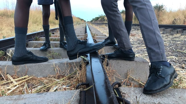 Die Füsse von vier Schulknaben. Alle tragen sie schwarze chice Schuhe.