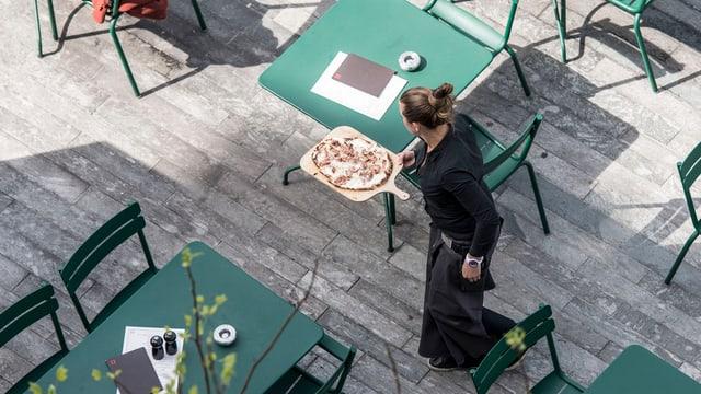 Kellnerin serviert eine Pizza auf einer Gartenterrasse mit vielen unbesetzten Plätzen.